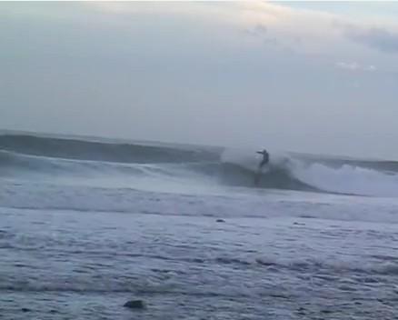 Un surfista sulle onde autunnali della baia di Squillace