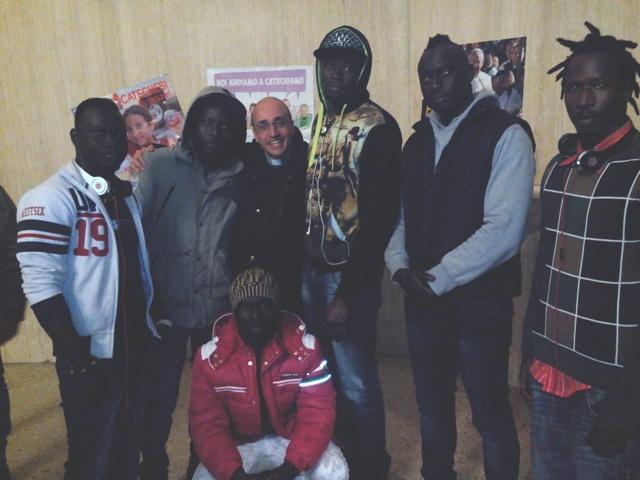 Don Roberto con alcuni migranti