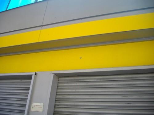Una delle saracinesche del distributore:in alto si intravede il foro lasciato dai colpi di pistola