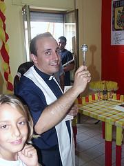 Sempre col sorriso: don Roberto mentre benedice un'abitazione